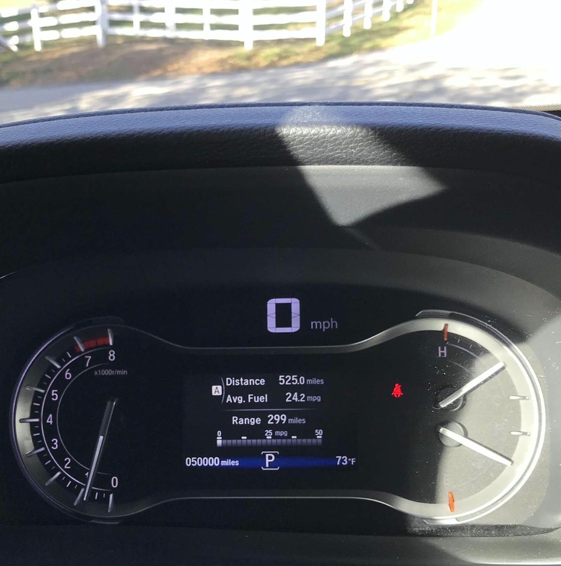 Car instrument cluster with dashboard reading 50000 miles.