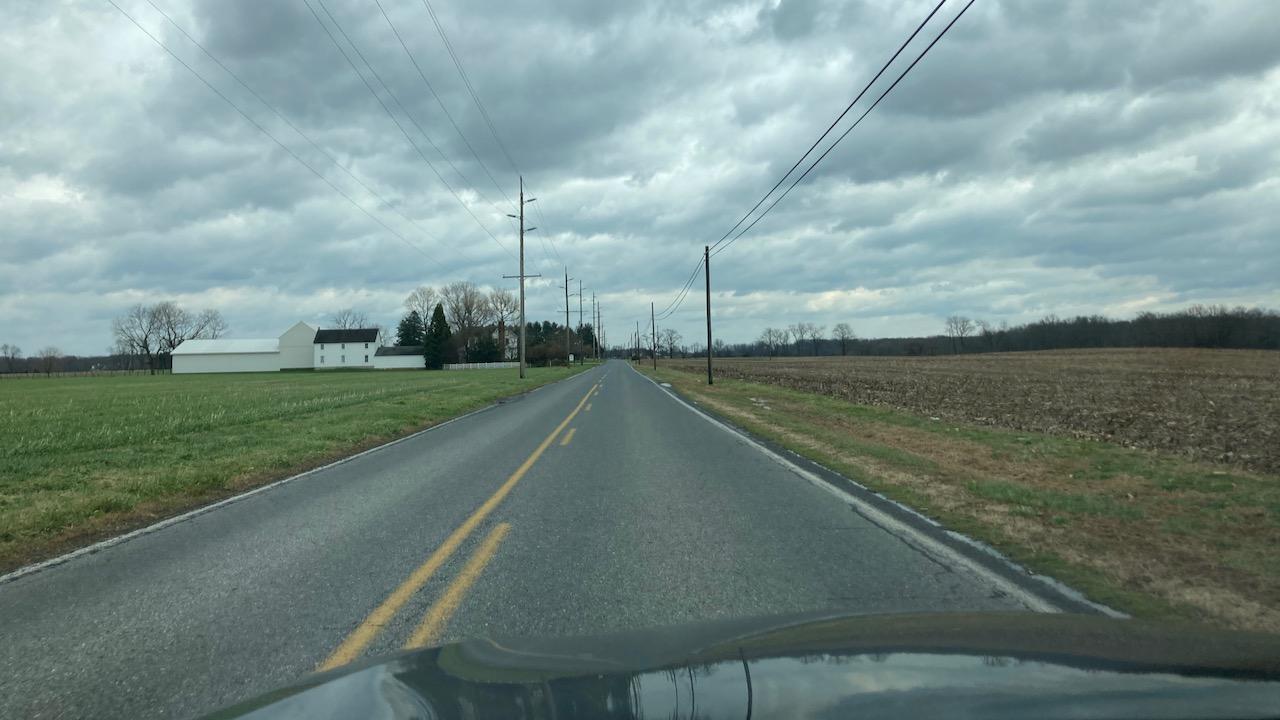 View of two-lane county road through farmland.