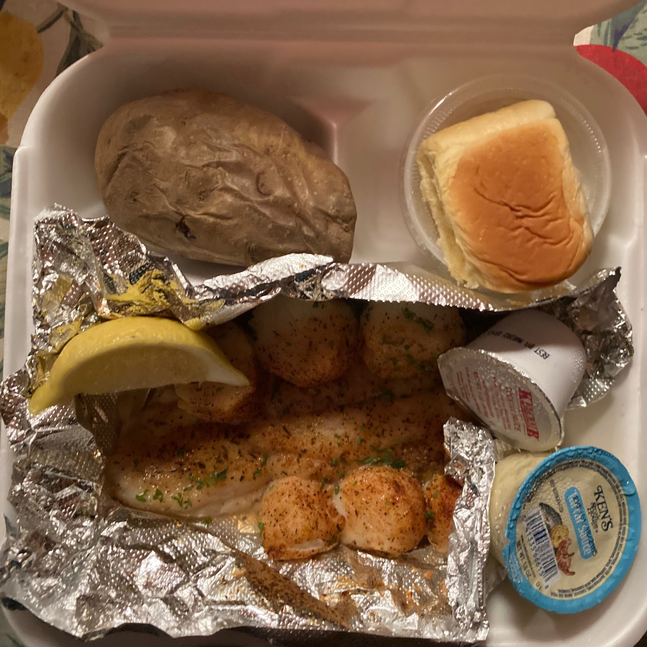 Styrofoam container with roll, baked potato, grouper, scallops, lemon, and sauces.