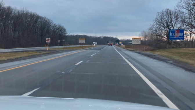 Highway I-80 with welcome sign for Indiana on side of road.