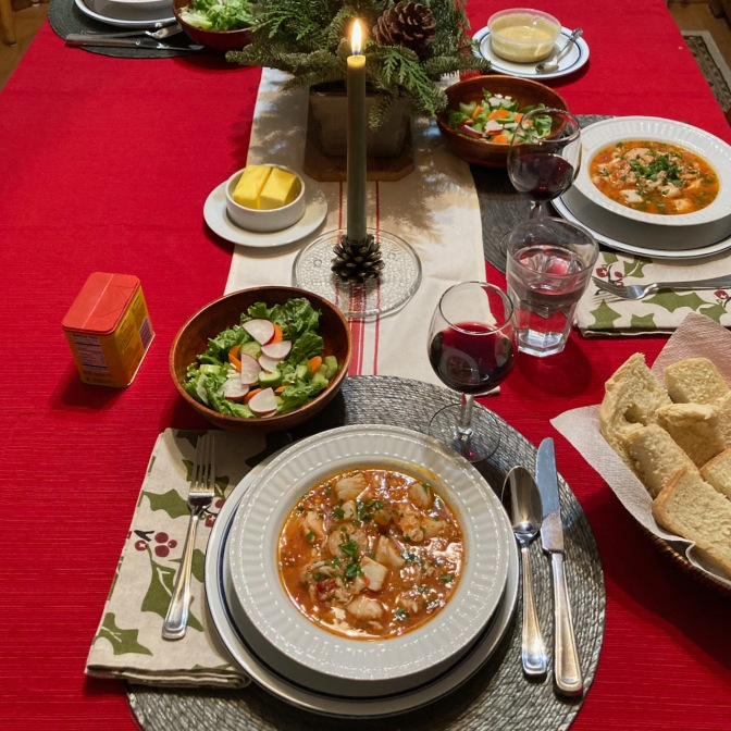 Table with red tablecloth, with seafood soup, salad, and bread on table.