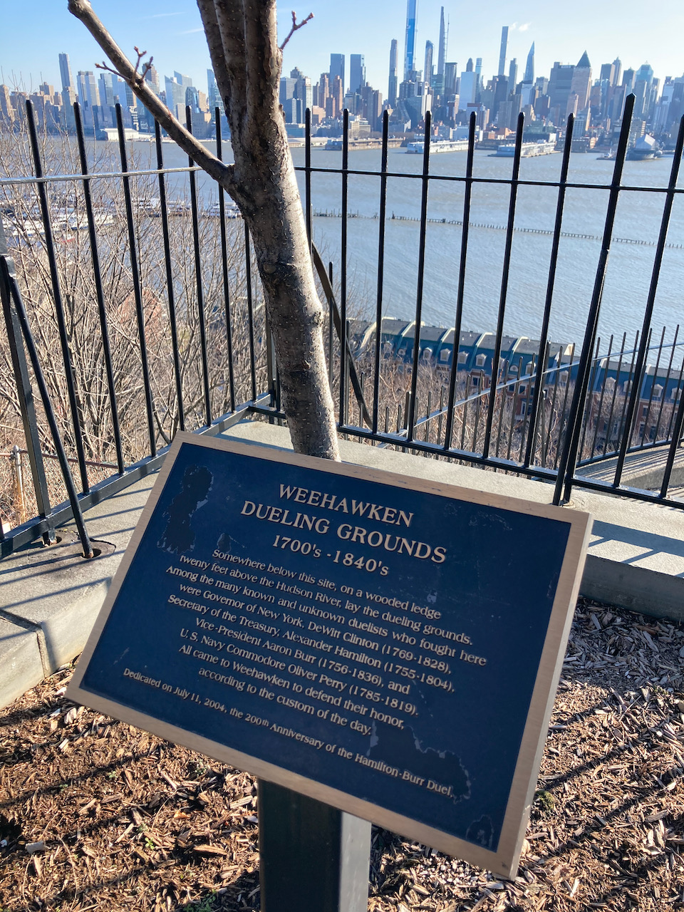 Plaque with description of Weehawken Dueling Grounds 1700s - 1840s, with view of Hudson River and Manhattan skyline in distance.