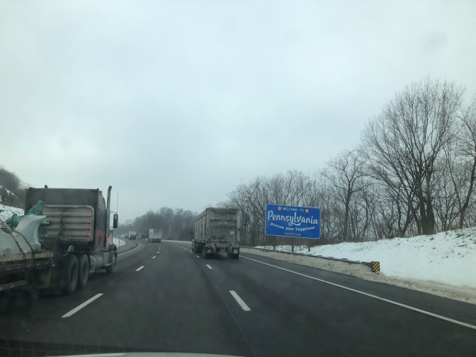 View of highway with sign that says WELCOME TO PENNSYLVANIA along right shoulder.