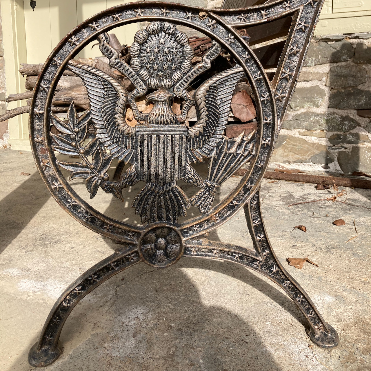 Wrought iron bench with seal of the President on the side.