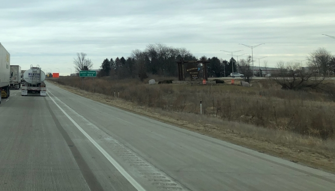 View of highway with sign for Wisconsin on the side of road.