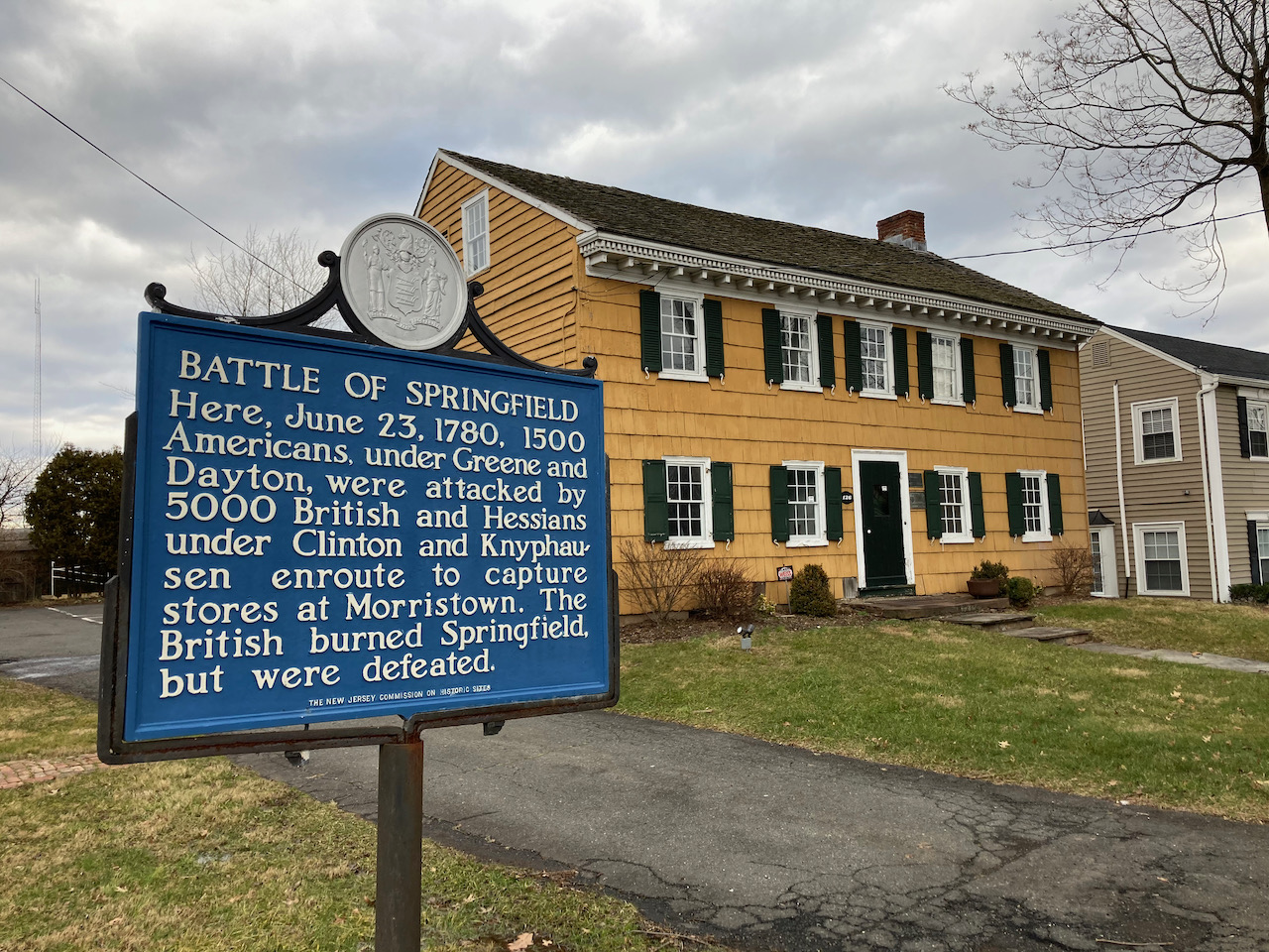 Exterior of the Osborn Cannonball House, with a sign outside that says BATTLE OF SPRINGFIELD HERE JUNE 23 1780, 1500 AMERICANS UNDER GREENE AND DAYTON WERE ATTACKED BY 5000 BRITISH AND HESSIANS UNDER CLINTON AND KNYPHAUSEN ENROUTE TO CAPTURE STORES AT MORRISTOWN. THE BRITISH BURNED SPRINGFIELD BUT WERE DEFEATED.