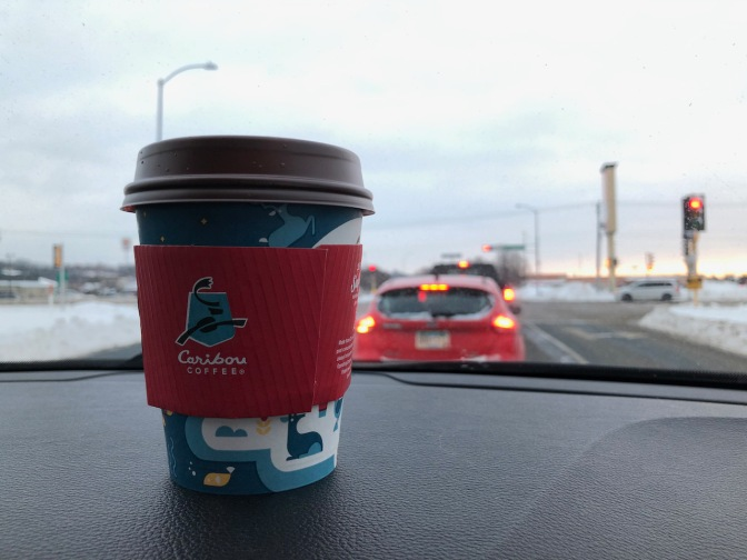 Cup of Caribou coffee on dashboard.