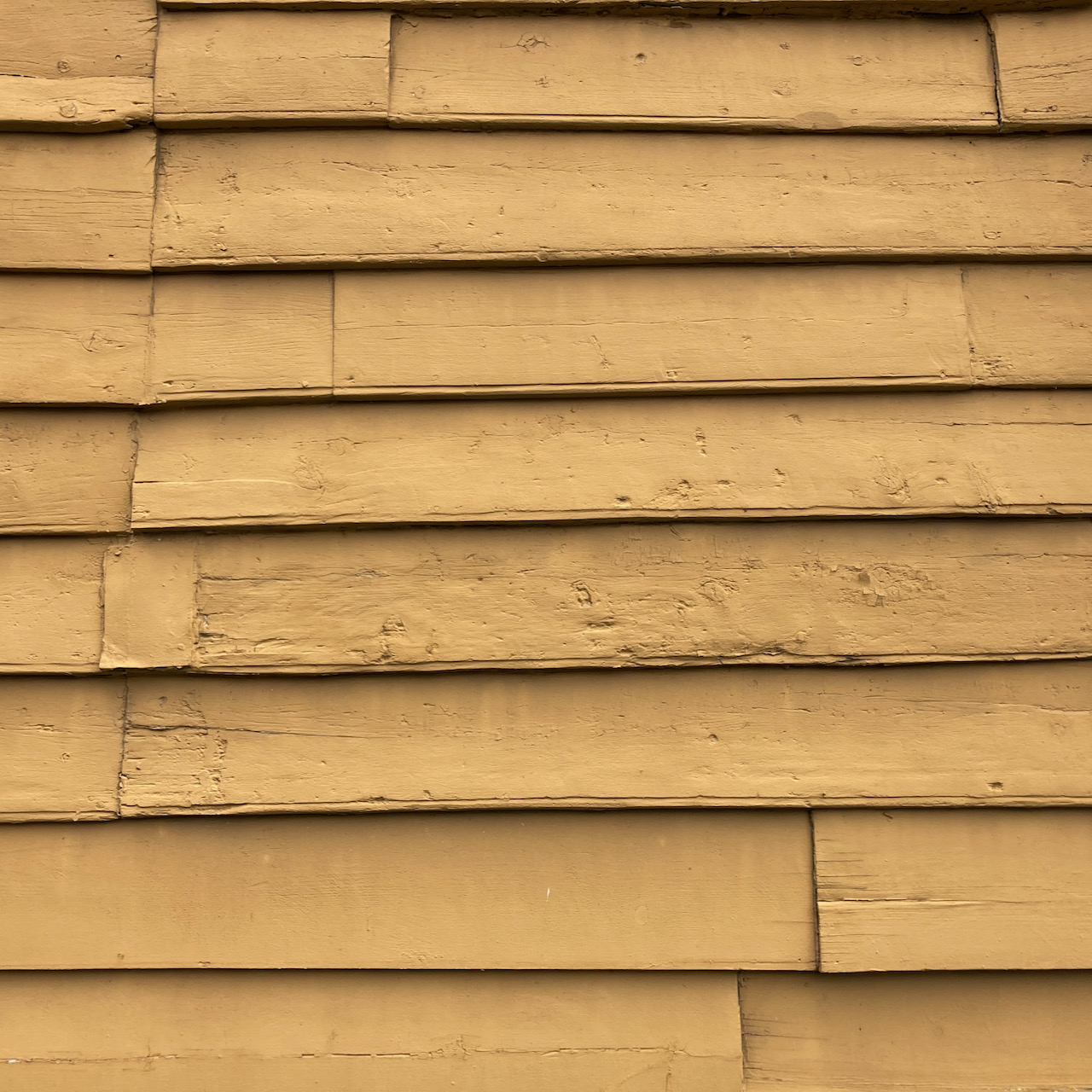 Clapboard siding, painted yellow.
