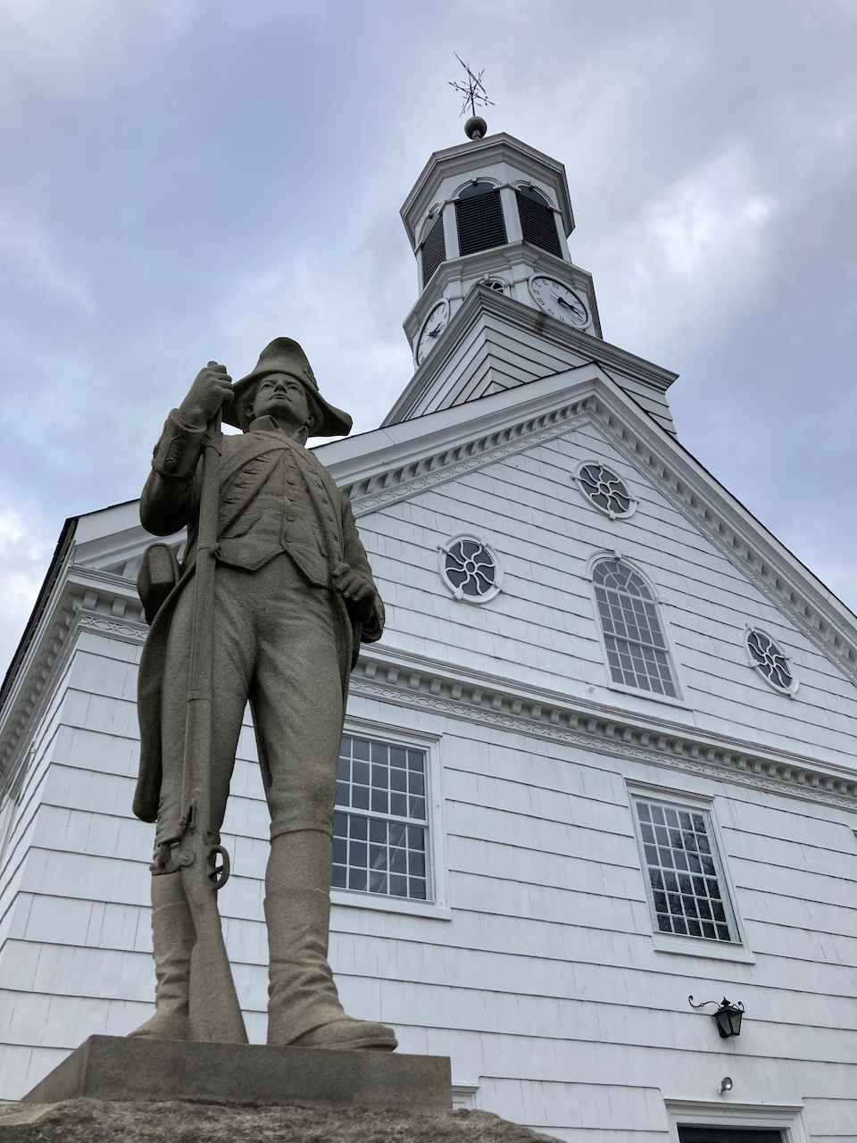 Colonial soldier in front of church.