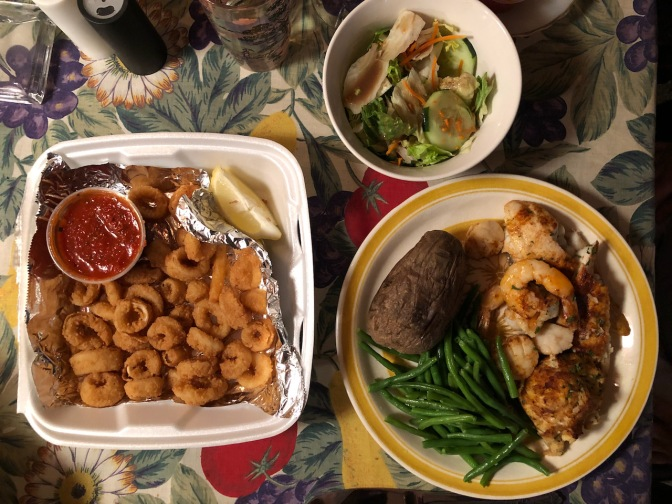 Table with container of calamari, bowl of salad, and a plate with baked potato, green beans, broiled fish, shrimp, and scallops.