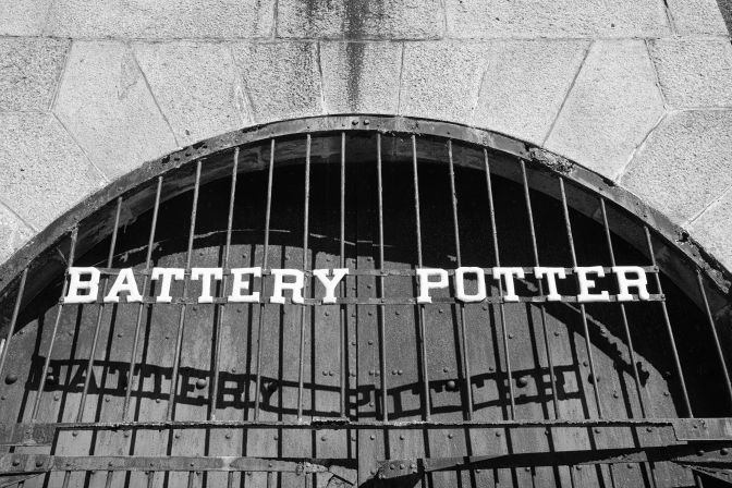 Barred metal doors that say BATTERY POTTER with shadow spelling same words on door.