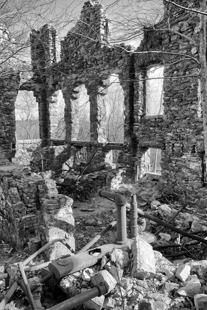 Ruins of interior of building, including pipework.