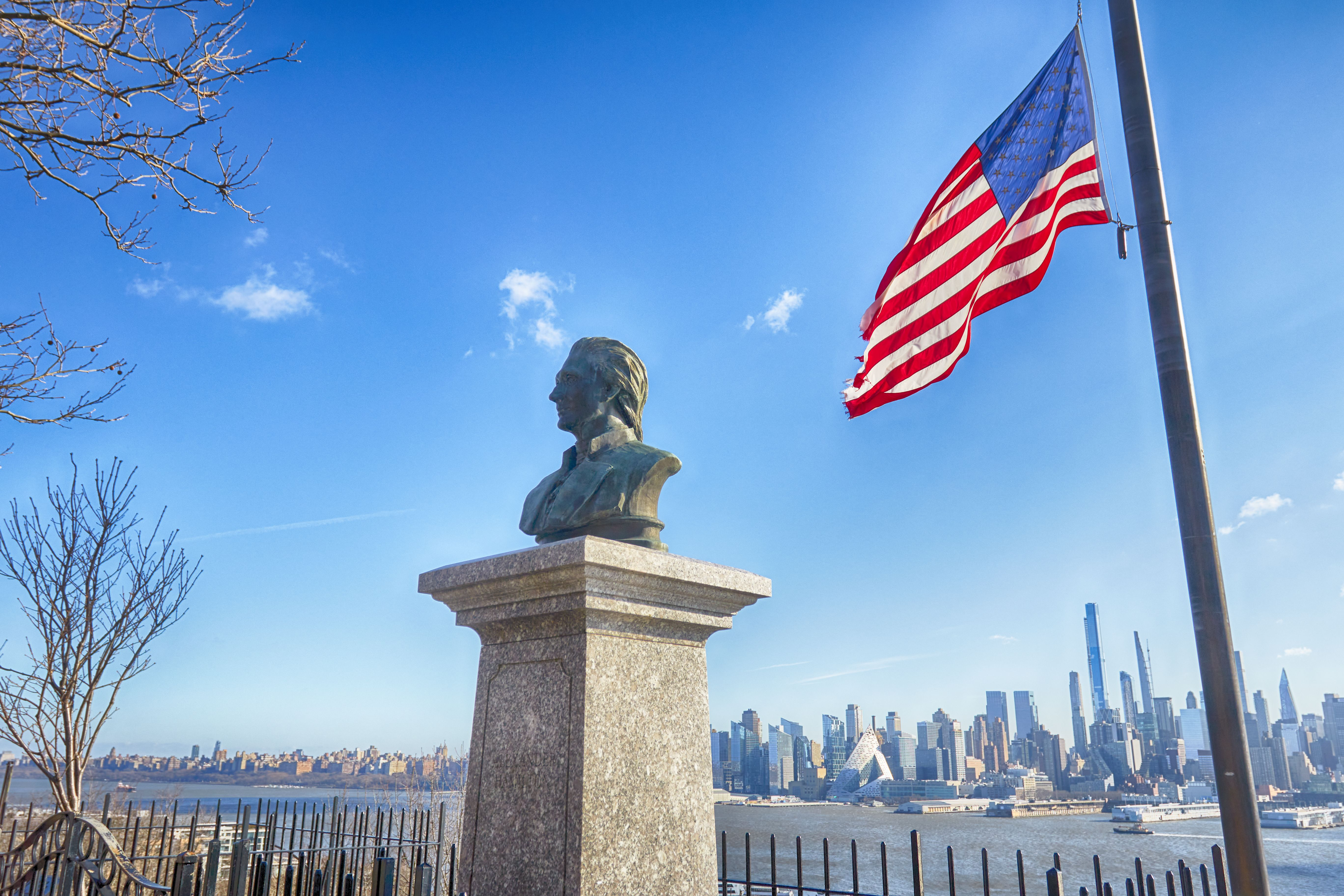 Bust of Alexander Hamilton on plinth, with an American flag at half-staff beside it. Manhattan is visible in the distance.
