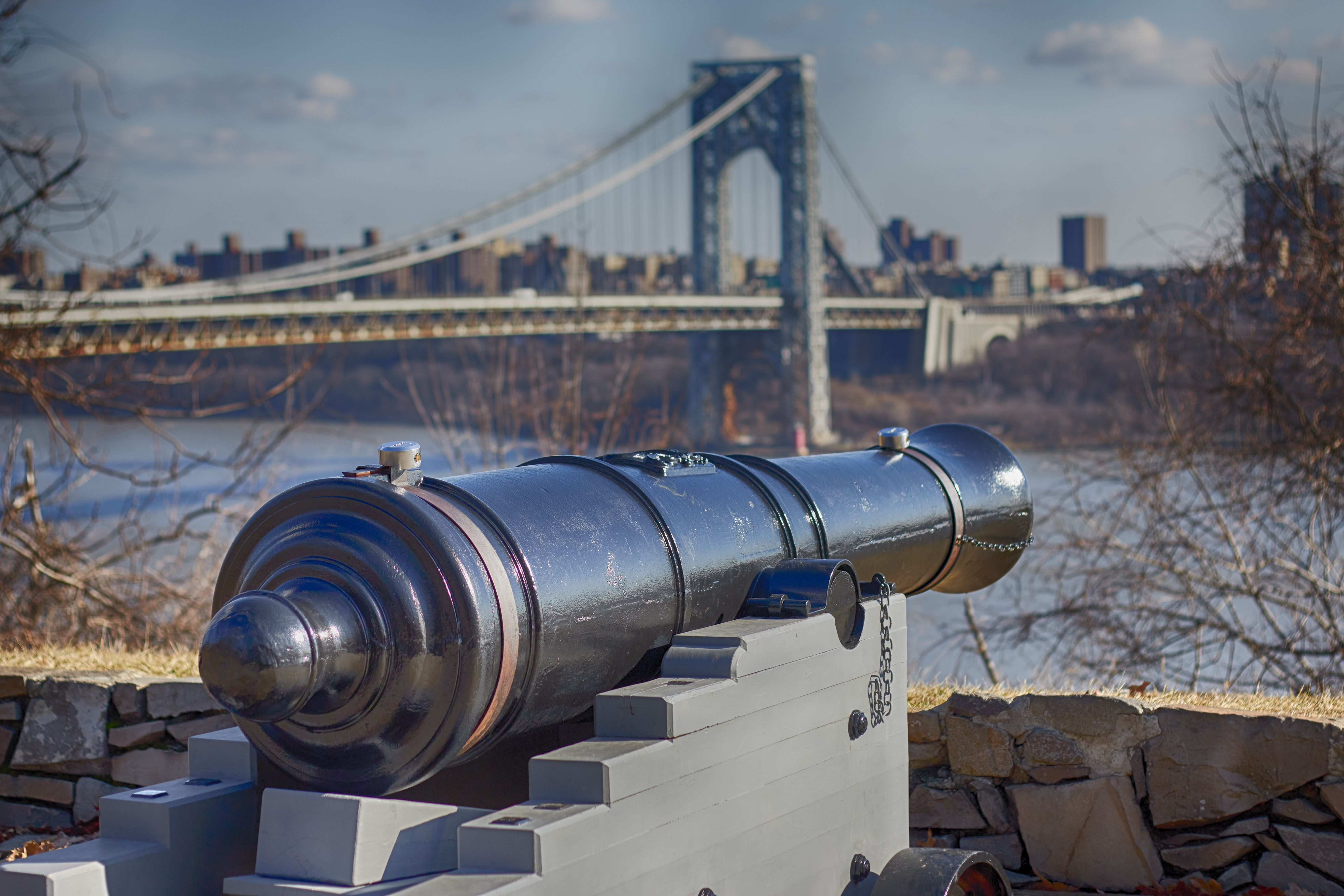 Cannon overlooking river, with George Washington Bridge in background.