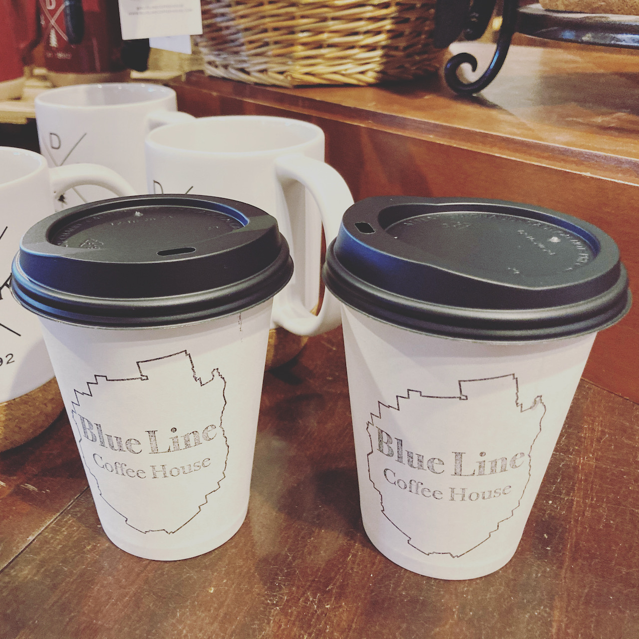Two paper coffee cups on wooden tables each cup says BLUE LINE COFFEE HOUSE.