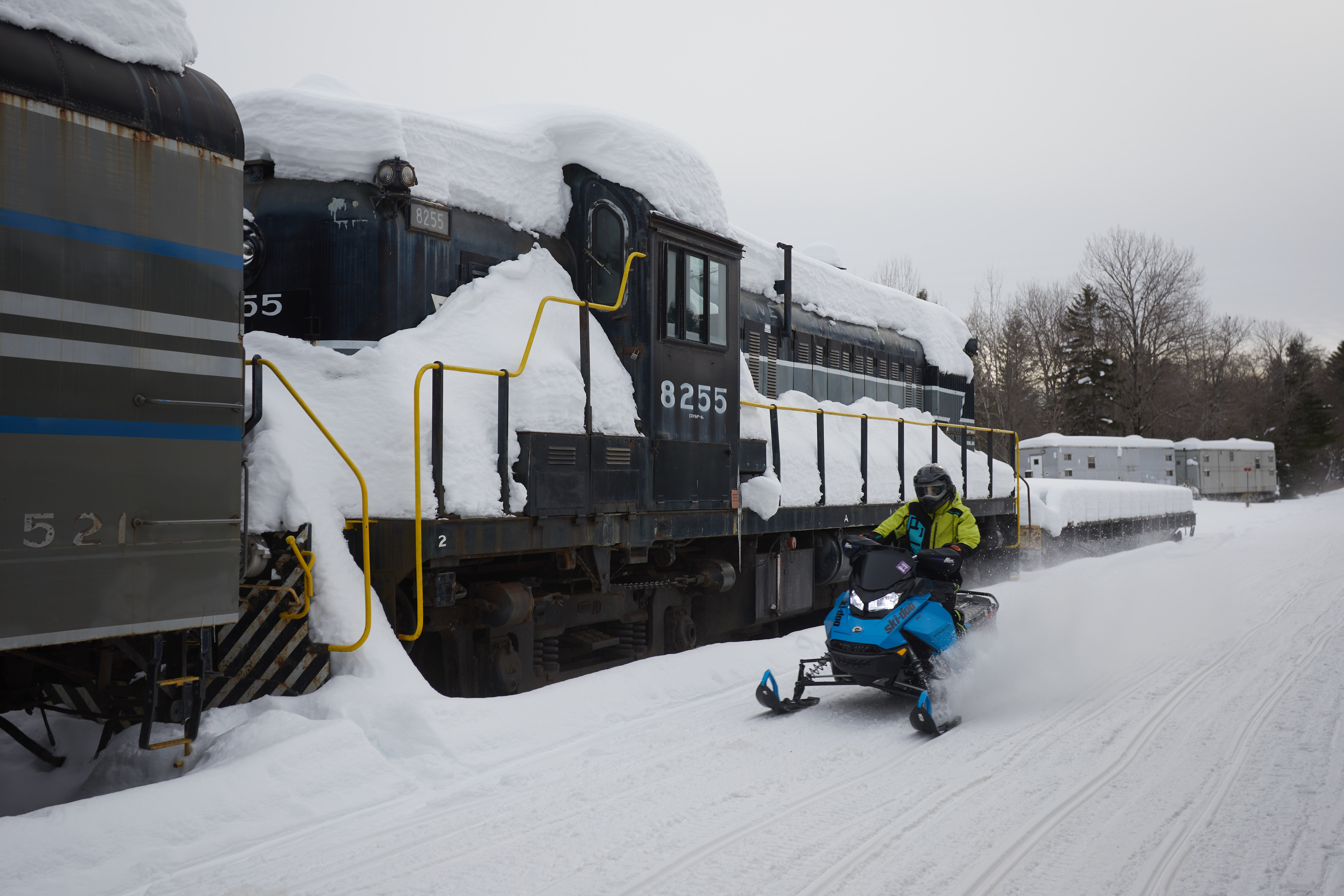 Snowmobiler speeding through train yards.