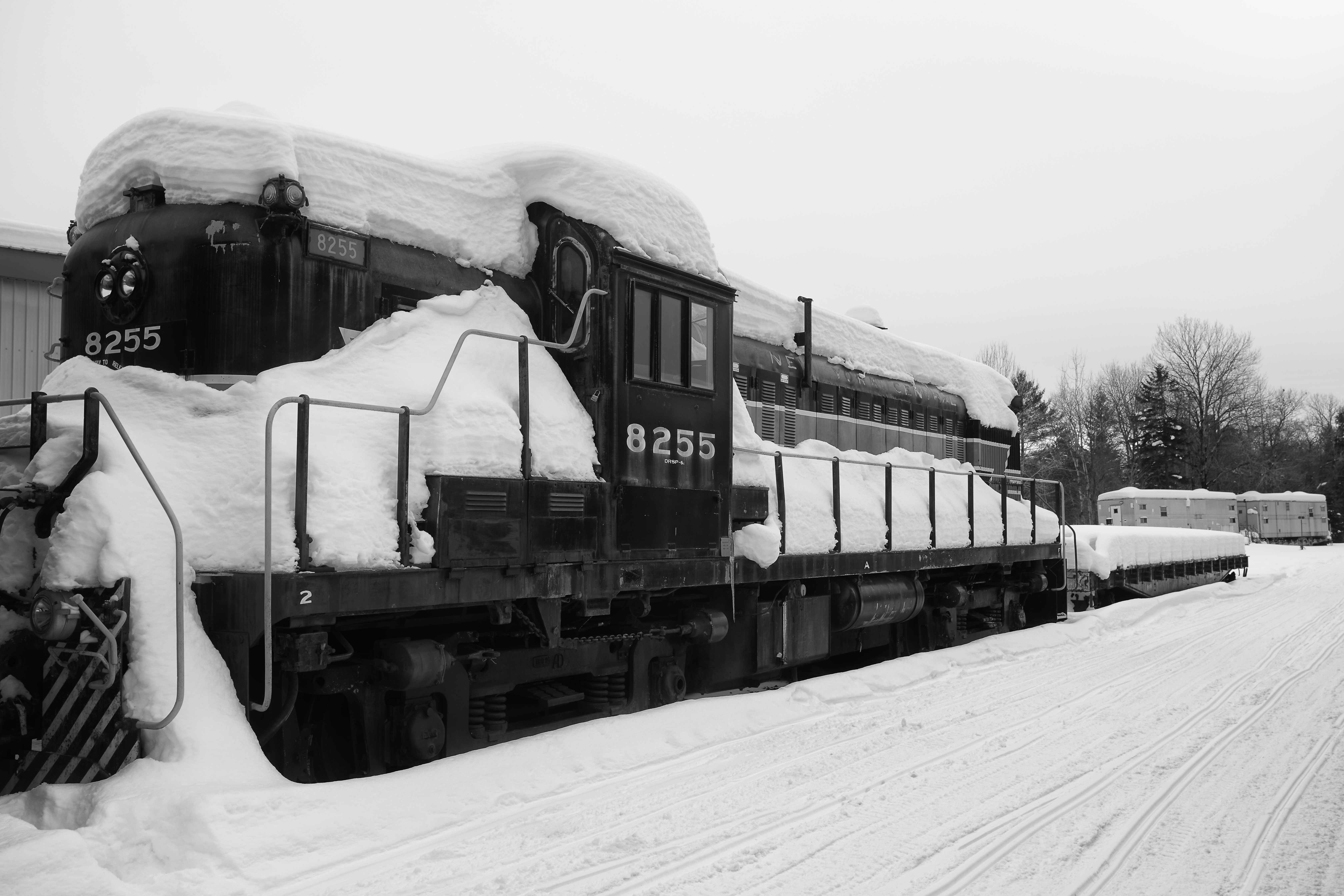 Black and white image of diesel locomotive covered in snow.