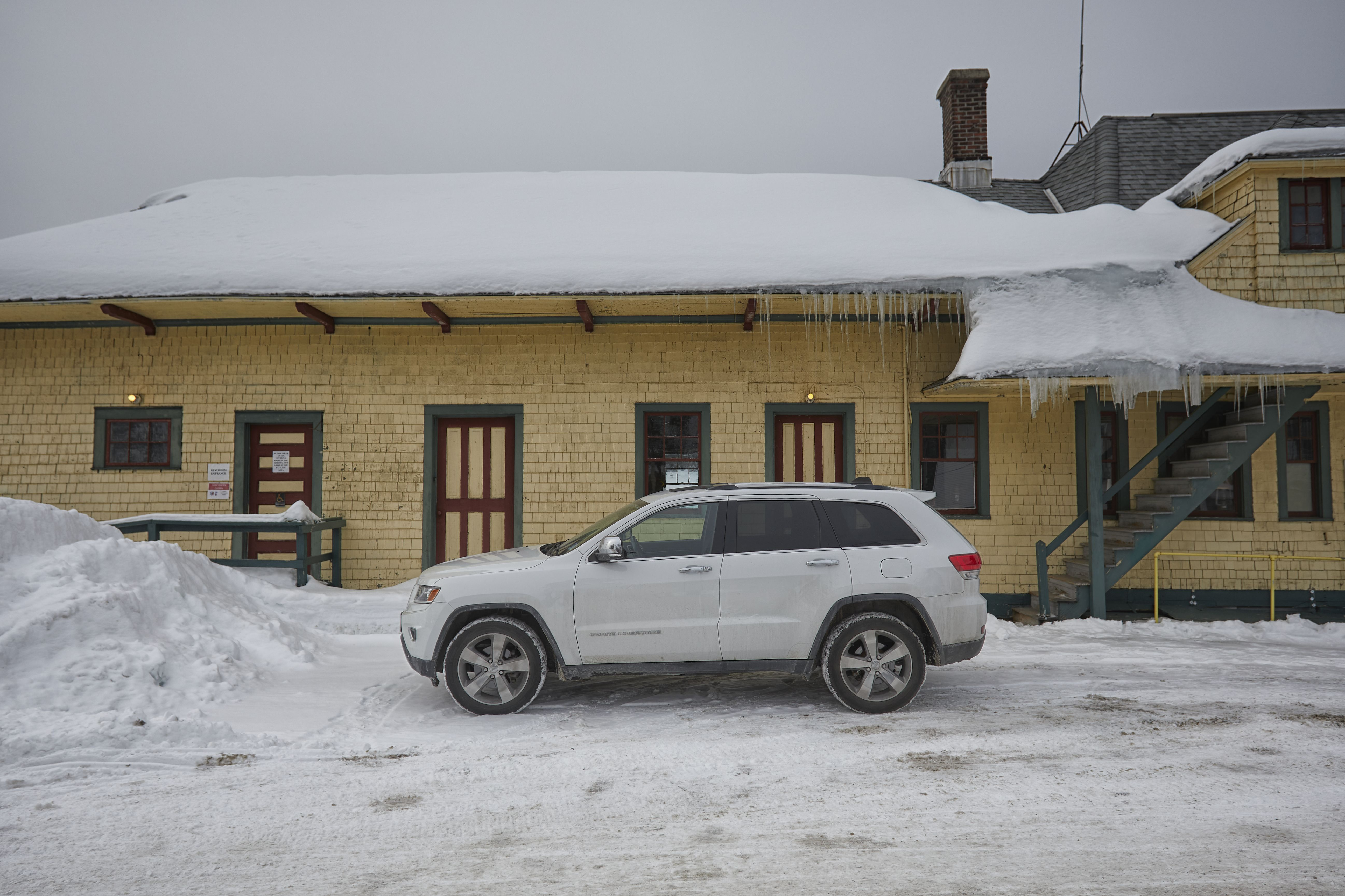White Jeep Grand Cherokee parked in front of Thendara Train Station.