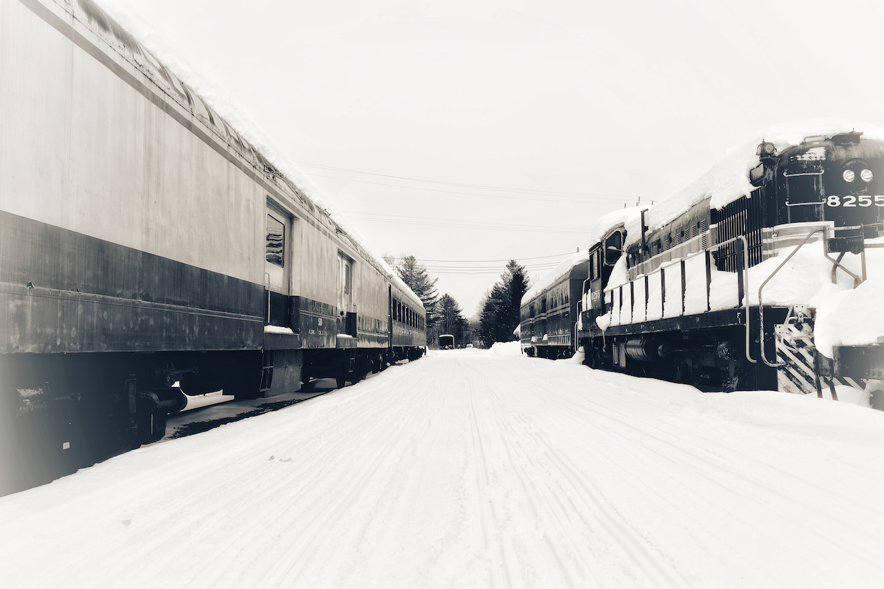 Trains on two parallel tracks in snow.