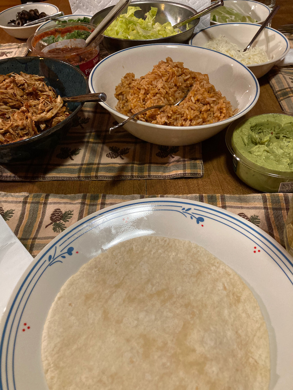 Table with Mexican rice, tortillas, guacamole, shredded chicken, salsa, cheese, lettuce, and black olives.
