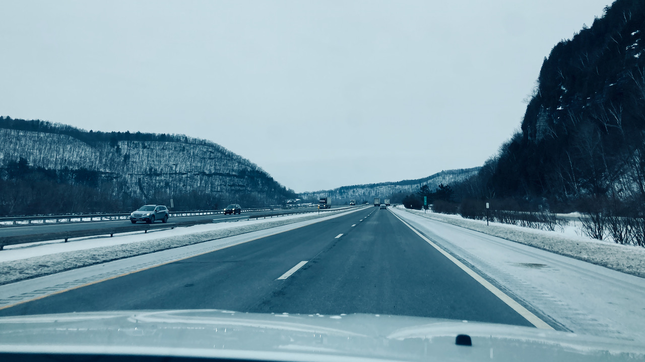 View of New York Thruway, with hillsides covered in snow.