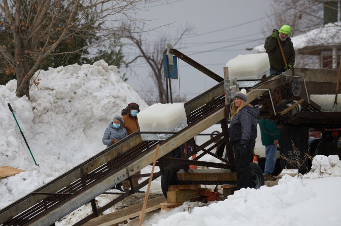 Workers gathered around conveyer belt bringing ice into truck along shore.