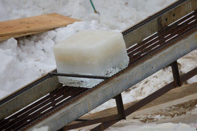 Block of ice ascending conveyor belt.