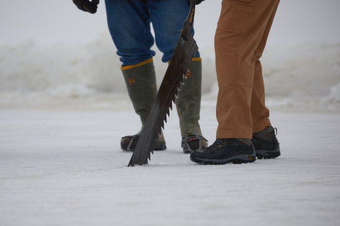 Volunteers cutting ice from lake.