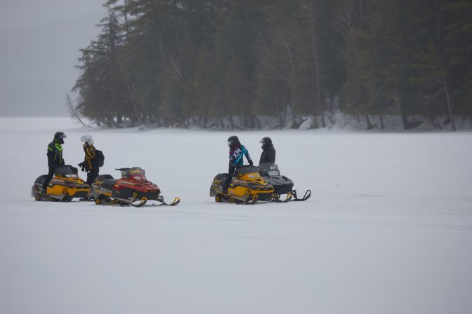 Snowmobilers parked on ice.