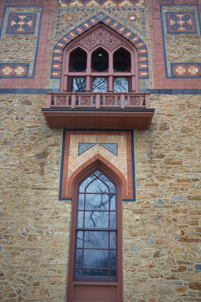Section of house include first-floor window and second-floor window with elaborate exterior designs.