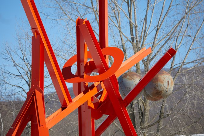Red metal sculpture with trees in background.