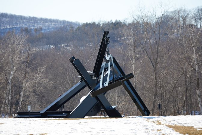 Metal sculpture with wooden bed hanging from crane arm.