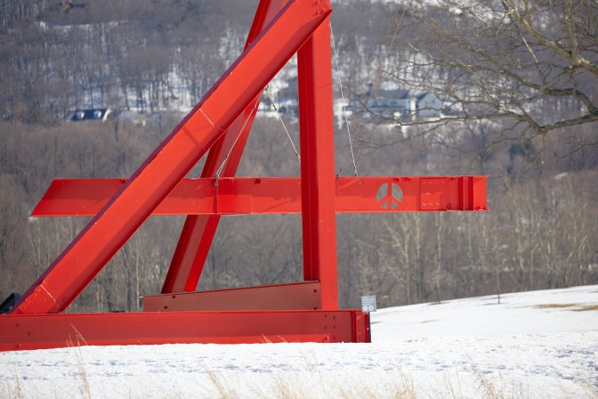 Red structure made of steel girders, with peace symbol on one.