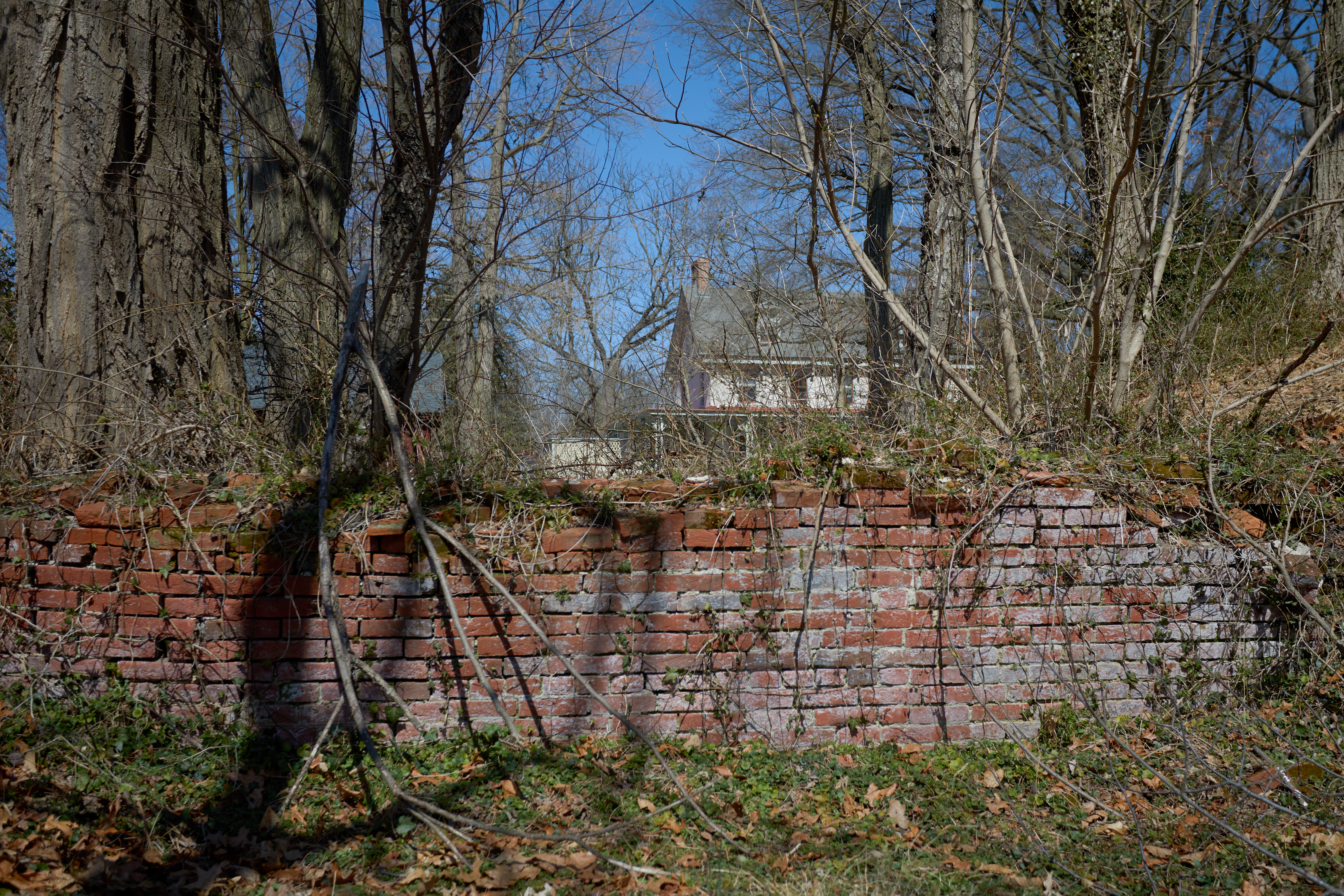Remnants of brick wall with mansion in distance.