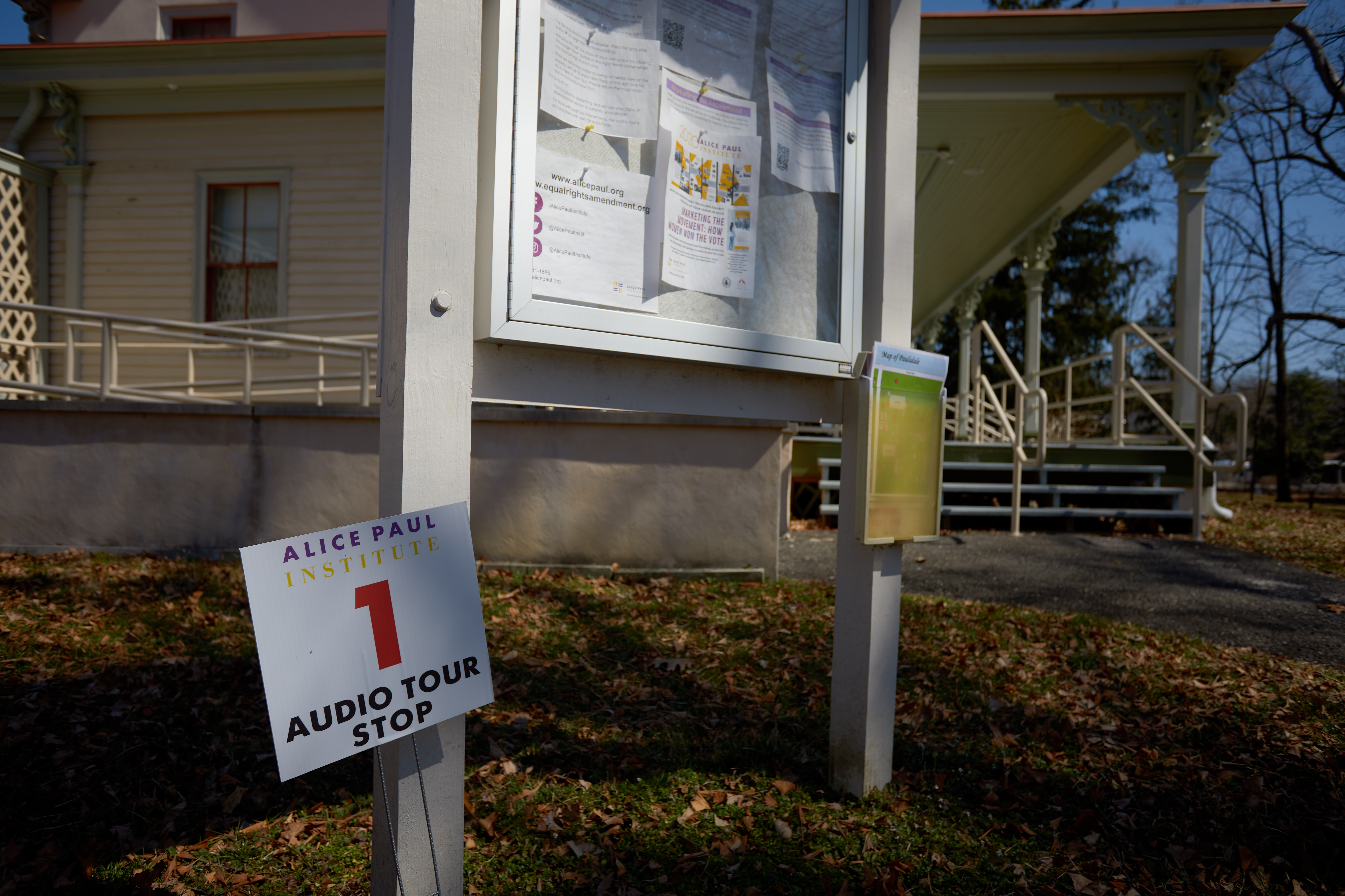 Signage outside Paulsdale mansion, with a small cardboard sign on lawn that says AUDIO TOUR STOP 1.