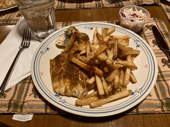 Blackened fish with french fries and coleslaw on plate.