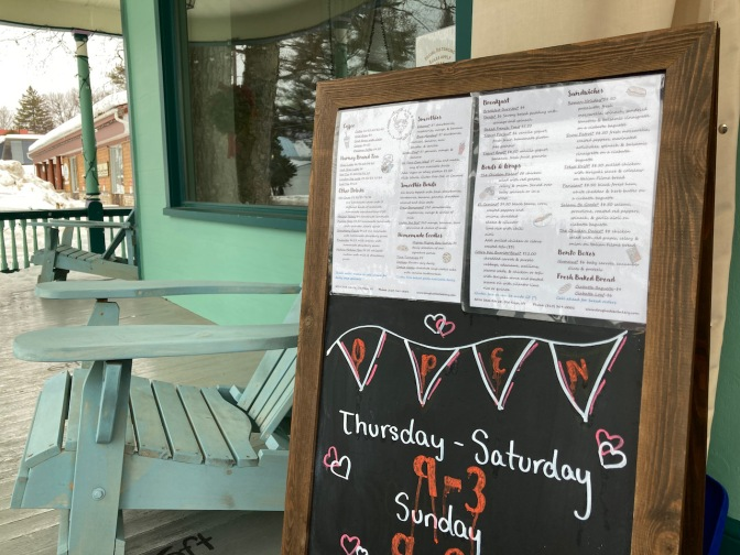 Sandwich board outside of cafe that has menu and hours of operation.