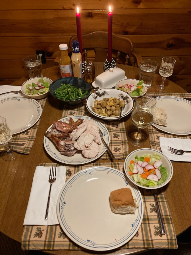 Table with place settings for three people, chicken, roasted potatoes, green beans, and salad.