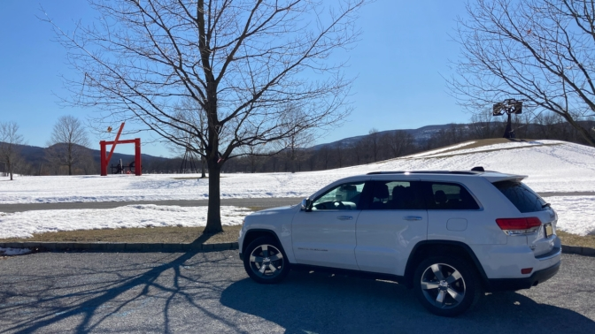 Jeep Grand Cherokee parked in front of field with sculptures.