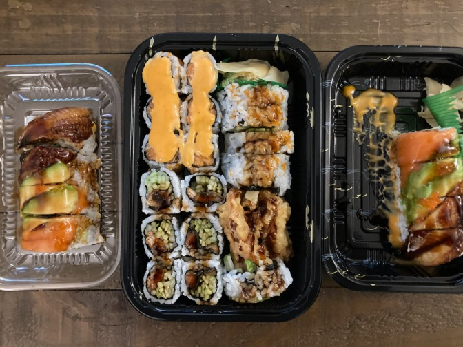 Various sushi in plastic to-go containers.