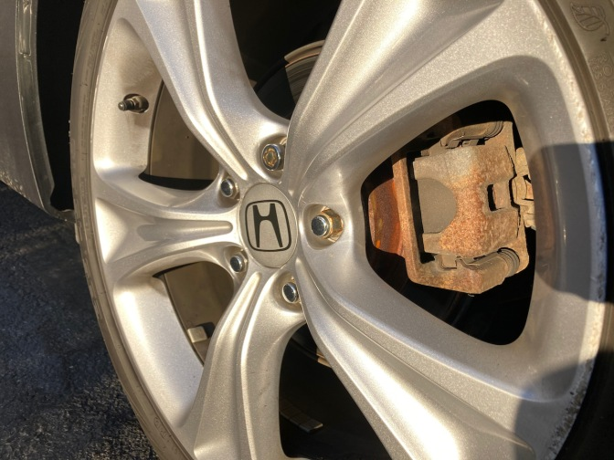 View of car wheel, with focus on brake caliper.