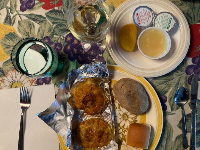 Plate with two crab cakes, baked potato, and roll, a glass of water, and a glass of wine.