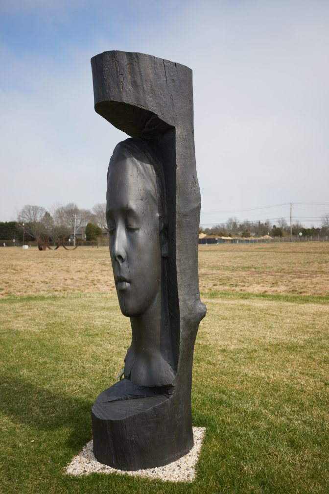 Sculpture of woman's head in cut away from stone.