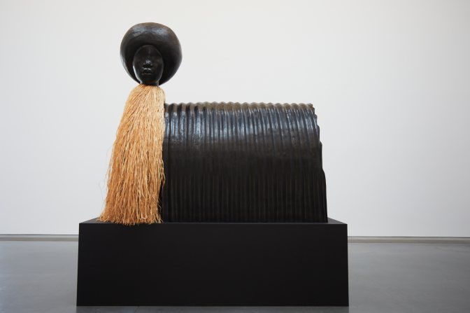 Sculpture of woman's head atop stand, with straw body.