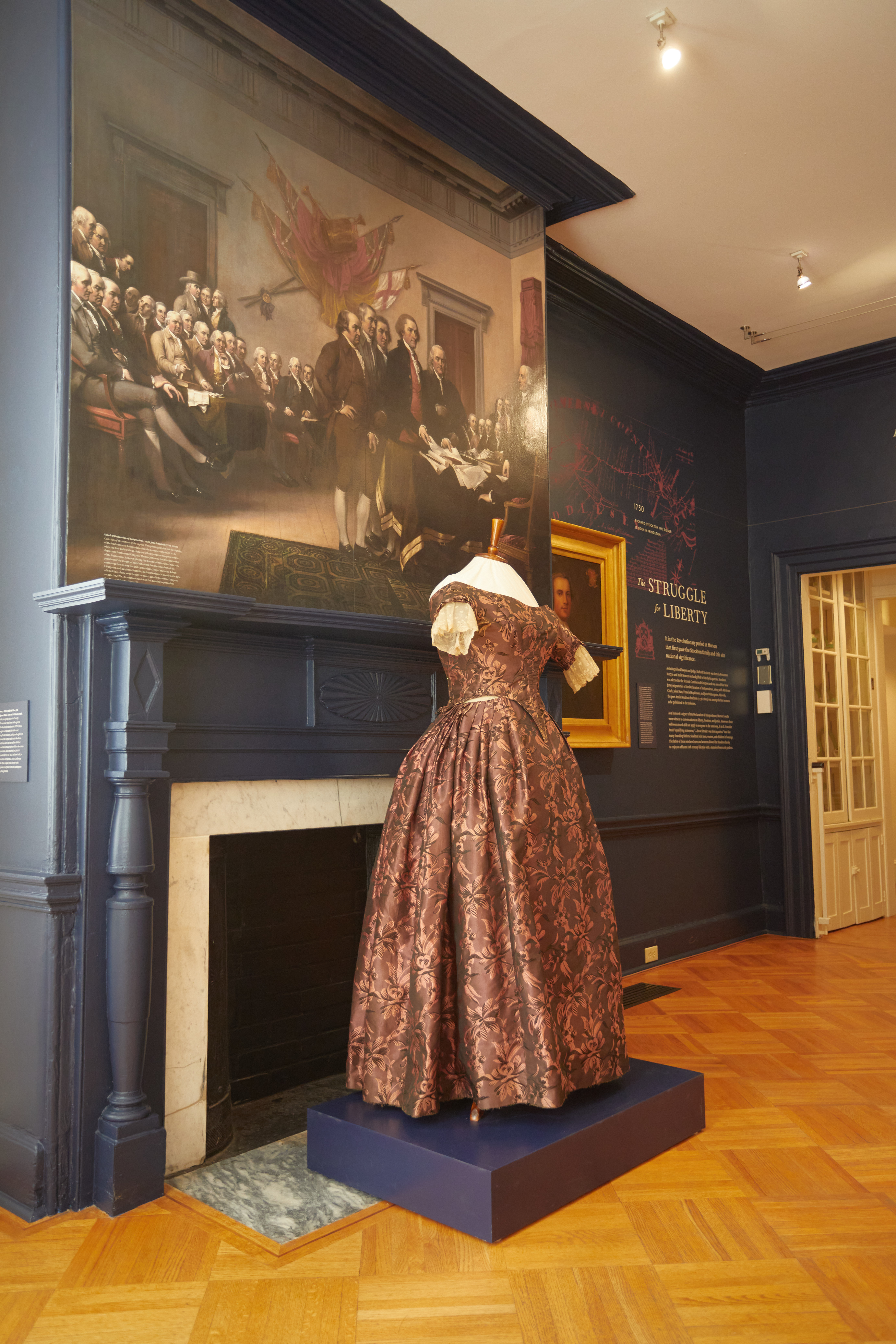 Room with woman's gown on display in front of mural of the signers of the Declaration of Independence.