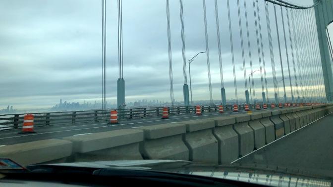 View of Manhattan skyline in distance from top of bridge.