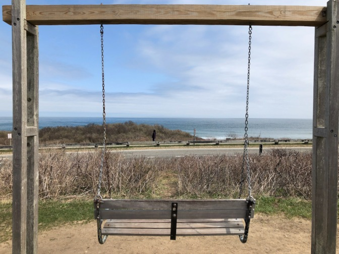 Swing bench with view of ocean in distance.