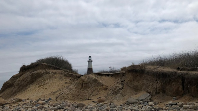 View of Lighthouse behind sand dunes.