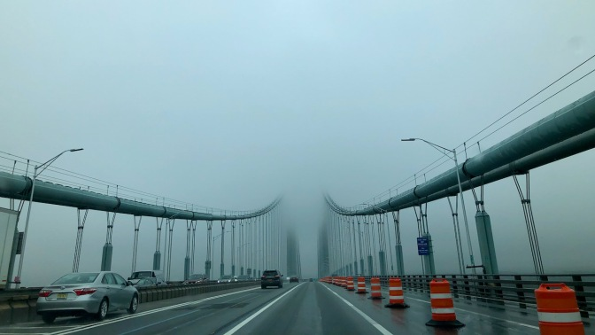 View of Verrazano Narrows Bridge from on bridge, with top structure disappearing into fog.