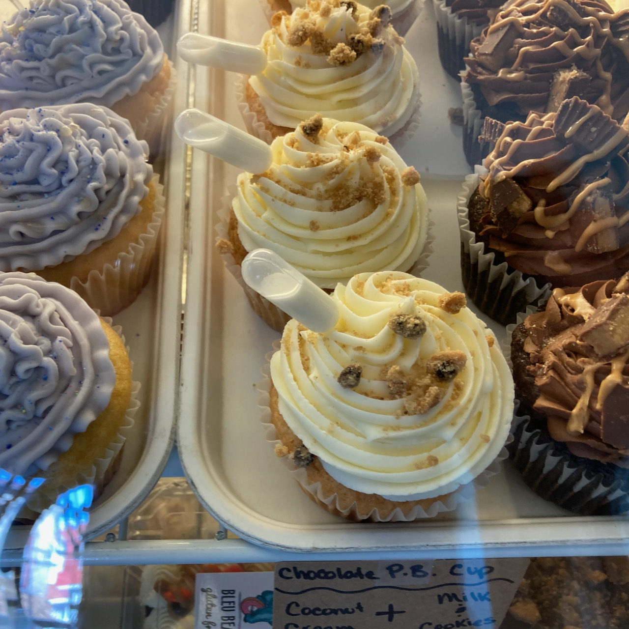 Gluten-free cupcakes under glass case.